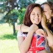 Two happy teenage girls sharing gossip and laughing — Stock Photo