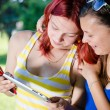 Two young female students sitting in park with tablet pc — Stock Photo #35716375