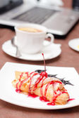 Apple croissant, cup of drink and laptop business lunch — Stock Photo