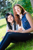 Two young female students sitting in park with tablet pc — Stock fotografie