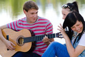 Three happy teen friends playing guitar in green summer park — Stockfoto