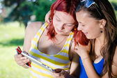 Two young female students sitting in park with tablet pc — Stok fotoğraf
