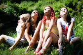 Four happy teen girl friends looking together in one direction — Stock Photo