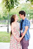 Joven pareja sonriendo felices cogidos de la mano — Foto de Stock
