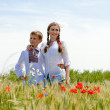 Teenage sister and little brother together on summer wheat fields — Stock Photo