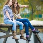 Two school girls sitting on river bridge — Stock Photo