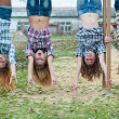 Stock Photo: Four young girls hanging upside down in park