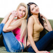 Portrait of two pretty young girlfriends or sisters on sofa — Stock Photo #37108461