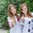 Stock Photo: Young women giving thumbs up
