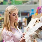 Mujer con rollos de papel pintado — Foto de Stock