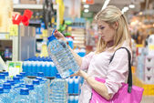 Woman buys a bottle of water in the store — Stock Photo