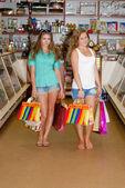 Två glada unga kvinnor med kassar och påsar — Stockfoto