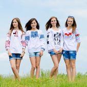 Four happy teenage friends posing in handmade blouses against blue sky — Stock Photo
