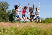 Quatre amis heureux adolescentes sauter haut dans le ciel bleu — Photo