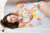 Lady in bath with flower petals — Stock Photo
