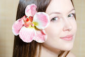 Beautiful girl face & flower. Perfect skin. — Stock Photo