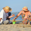 Happy mature couple playing at seashore on sandy beach — Foto de stock #37125613