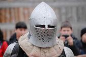 Knight in helmet before festival battle with spectators — Stock Photo