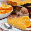 Stock Photo: Piece of Lemon and almond pie on plate with oranges