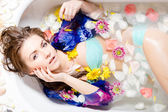 Lady taking a bath with flower petals — Stock Photo