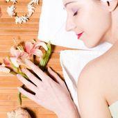 женщина, расслабиться во время массажа с цветами — Стоковое фото