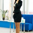 Woman at office workplace with mobile cell phone — Stock Photo