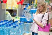 Woman buys a bottle of water — Photo