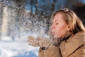 Beautiful blond young woman blowing Snow outdoors — Stock Photo