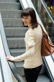 Jonge vrouw op roltrap — Stockfoto