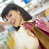 Happy woman holding shopping bags and smiling — Stock Photo