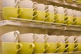 Lot of yellow & cream-white cups on shelf — Stock Photo
