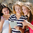 Stock Photo: Three girls friends looking on tablet pc