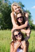 Three happy teen girls embracing against blue sky — Stock Photo