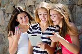 Three girls friends looking on tablet pc — Stock Photo