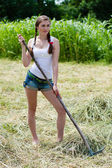 Beautiful young woman working with rake on dry hay on summer day — Stock Photo