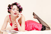 Young dreamy sexy pinup woman wearing pink dress and stockings — Stock Photo