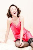 Young happy laughing pinup woman wearing pink dress and stockings — Stock Photo