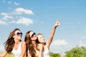 три счастливые девушки, показывая вверх, в голубое небо — Стоковое фото