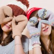 Women girl friends wearing knitted gloves and hat showing binoculars — Stock Photo