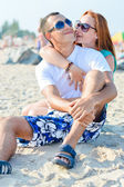 Young happy couple sitting on sandy beach — Stock Photo