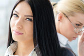 Two beautiful young women brunette & blond co-workers — Stock Photo