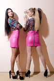Women wearing same bright leather dresses — Stock Photo