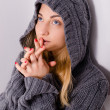 Beautiful young blond woman girl in hood praying & looking up — Stock Photo