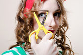 Woman looking at camera through scissors — Stock fotografie