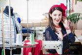 Funny young pinup woman with sewing machine and measuring tape — Stock Photo