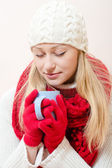 Woman wearing scarf and gloves with cup of drink — Stockfoto