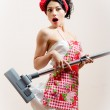 Pretty housewifely attractive young woman sexually funny pin-up girl is surprised because the vacuum cleaner eats her dress portrait — Stock Photo
