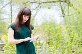 Girl standing with tablet pc computer outdoors — Stock Photo