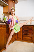 Young beautiful super flexible woman pinup girl wiping glass in purple gloves at the kitchen with leg-split — Stock Photo