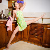 Young beautiful super flexible woman pinup girl in purple gloves at the kitchen with leg-split — Stock Photo